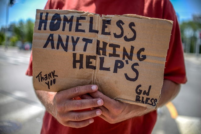 A homeless man holds a sign seeking a handout. Augusta commissioners say they're seeing more panhandling around the city and that solutions are needed.