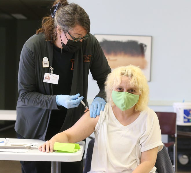 Massillon resident Gina Durst (right) receives a COVID-19 vaccination from registered nurse Christine Gogerty, of the Massillon Health Department, on Wednesday morning at the agency. The city Health Department hosted a vaccine clinic Wednesday that was to serve up to 130 people. Another clinic is slated for next week.