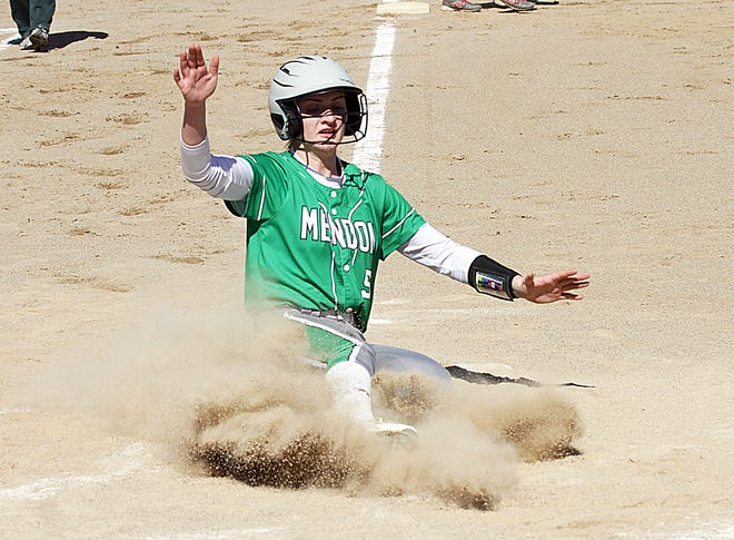 Mendon's Kara Swan slides safely into home plate to score a run for the Lady Hornets in prep softball action Tuesday.