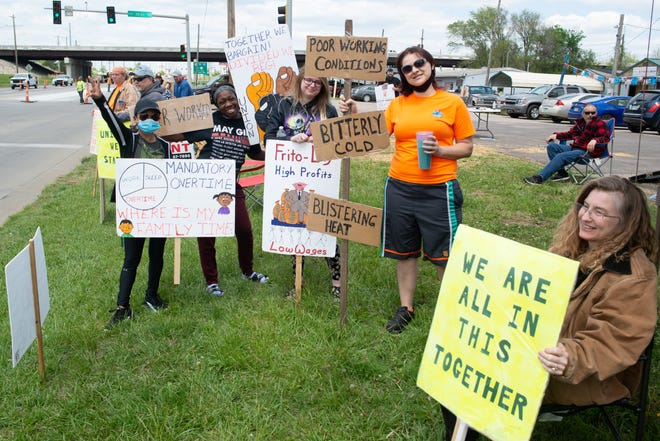 Union members and those supporting fair wages for Frito-Lay workers stand with signs at a picket outside the Topeka plant earlier this year.