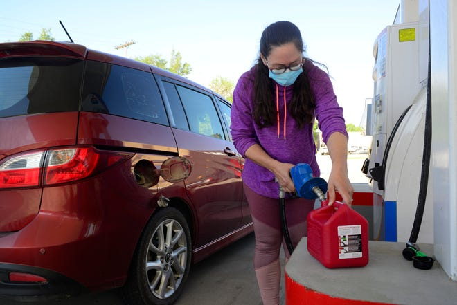 Ashley Patrick, Silver Lake resident, fills up a secondary gas can for her mower Wednesday morning from Max's Amoco gas station, 1301 S.W. Gage Blvd.