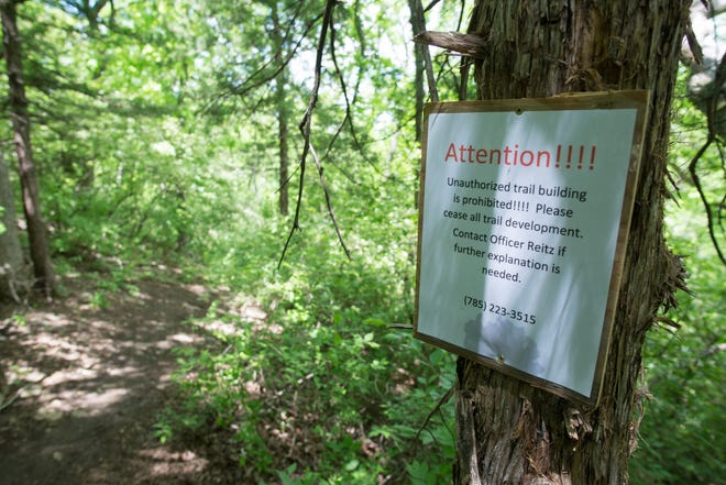 Posted at the start of a new downhill trail at Kaw Valley State Park is a sign informing trail builders that unauthorized work is prohibited. The sign includes the contact information of officer Tony Reitz, regional supervisor for Kansas department of wildlife, parks and tourism.