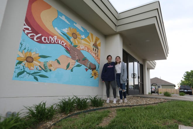 Bella Lujerrne, left, and Elly Keyes designed a mural that was painted on the side of Milk and Honey Coffee Co., 2200 S.E. 29th St.