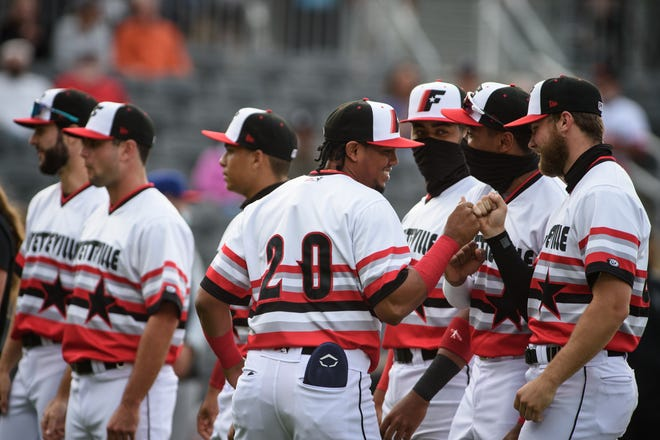 Yeuris Ramirez (20) and Woodpeckers teammates line up prior to their 10-1 home-opening win over the Cannon Ballers on Tuesday, May 11.