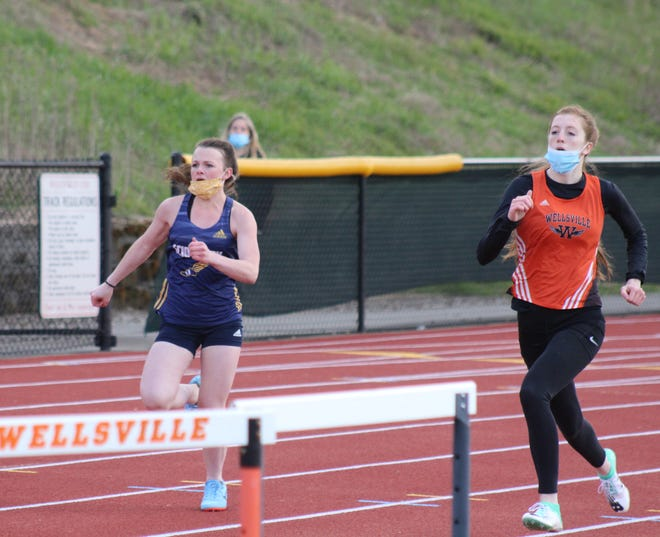 Wellsville's Brooklyn Stisser, right, and Scio's Lexi Crossley race in the 100 Tuesday evening in Wellsville.