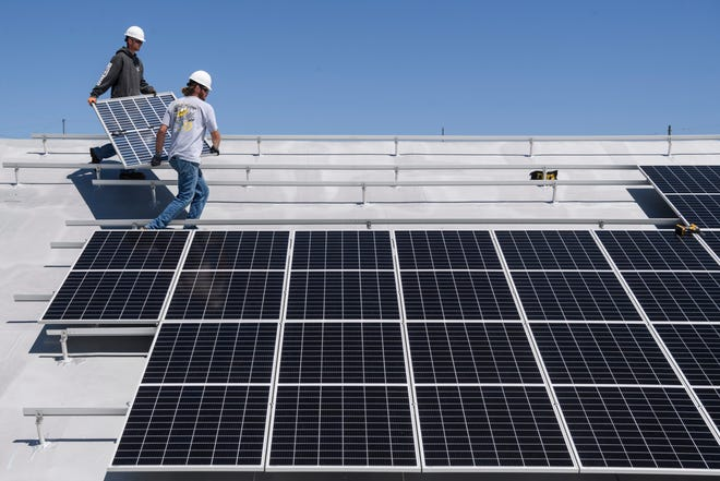 Spencer Baumholser, top, and Corey Kimball install and connect solar panels for Morton Solar, LLC on the top of the Lensing Building Specialties and Architectural Sales building in Evansville, Ind., Wednesday morning, May 12, 2021.