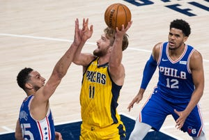 May 11, 2021; Indianapolis, Indiana, USA; Indiana Pacers forward Domantas Sabonis (11) shoots the ball while Philadelphia 76ers guard Ben Simmons (25) defends in the first quarter at Bankers Life Fieldhouse.