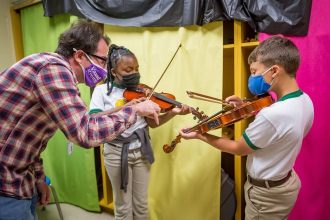 Teacher Jason Harrington with Aubrie Broussard, 10, fourth-grader and  Clayton Broussard, 11, fifth-grader playing fiddle at LeBlanc Elementary in Abbeville Wednesday, May 12, 2021.