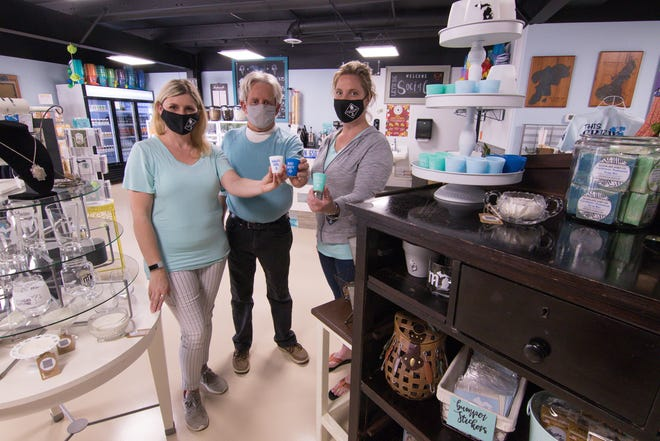 From left, Melissa Kunnert, dad Kerry Klave and Anna Teachworth hold shot glasses made of silicone Wednesday, May 12, 2021, at the NautiMI on the River store on the Huron River in Dexter Township.
