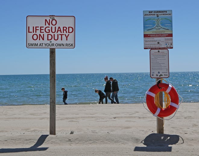 The vacationing Bender family from Bartlett Illinois, father Paul, from right, mother, Jackie, and sons Cullen and Caiden, walk past a no lifeguard on duty sign posted at Bradford Beach in Milwaukee Wednesday. Like last year, Bradford Beach will most likely not have lifeguards this year. Milwaukee County Parks isseeking around 300 strong swimmers for lifeguard positions, and if they don't find them, some pools and beaches won't open this summer.