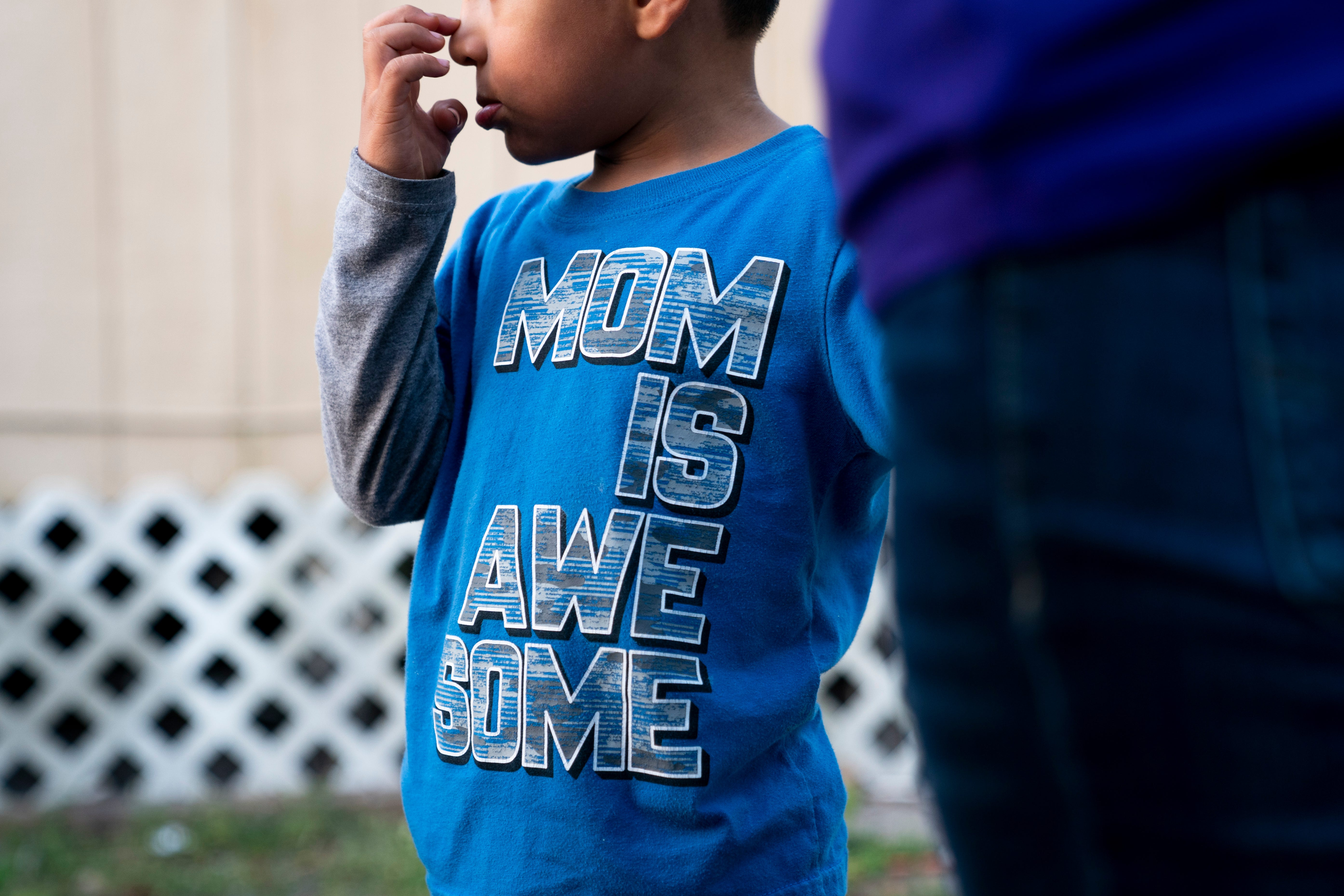 Juliana's son stands with her outside their home in Immokalee. Juliana is an undocumented farmworker, and her family has struggled financially during the pandemic because of limited work and family members contracting COVID-19.