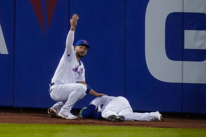 New York Mets' Michael Conforto, left, calls for a trainer for Albert Almora Jr. after Almora ran into the wall during the eighth inning of the team's baseball game against the Baltimore Orioles on Tuesday, May 11, 2021, in New York. (AP Photo/Frank Franklin II)