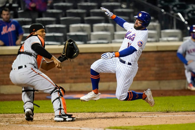 New York Mets' Kevin Pillar (11) slides past Baltimore Orioles catcher Pedro Severino to score during the ninth inning of a baseball game Tuesday, May 11, 2021, in New York. The Mets won 3-2. (AP Photo/Frank Franklin II)