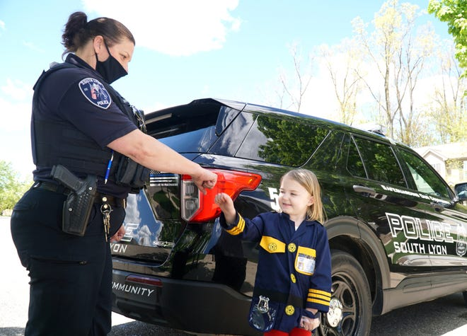 Kacie Zwiesele trades a fist-bump with South Lyon Police Officer Audra Baker on May 12, 2021.