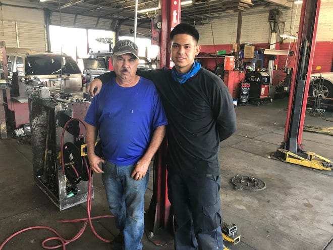 Jose Ramon Garcia, 59, (left) and his son, Ernesto Garcia, 19, an ASU business student, at the tire and auto repair shop the elder Garcia owns in the McDowell Square Shopping Center in Maryvale.