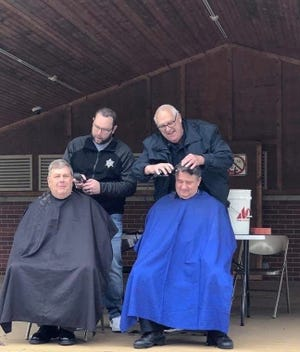 Evans Ehardt (top left) and Lexington Police officer Dave Hall (top right) shave Sanilac County Sheriff Paul Rich's and Lexington Police Chief Larry Sheldon's heads after the community raised nearly $11,000 for Ehardt, who has cancer.