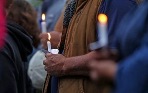 People gather in a park in Eden, Texas on Tuesday, May 11, 2021, for a candlelight vigil in honor of two Concho County sheriff's deputies who were killed in the line of duty on Monday.