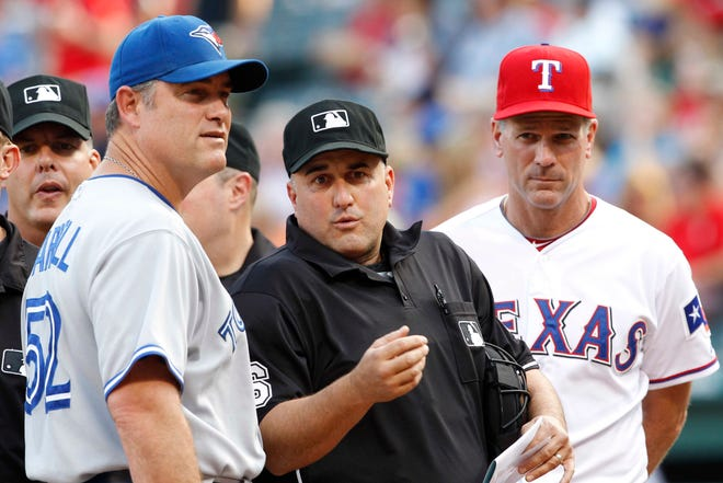 May 25, 2012; Arlington, TX, USA; Home plate umpire Eric Cooper (second from right) talks to Toronto Blue Jays manager John Farrell (52) and Texas Rangers third base coach Dave Anderson (right) before the game at Rangers Ballpark in Arlington. Mandatory Credit: Jim Cowsert-USA TODAY Sports