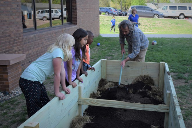 Three members of the Boys and Girls Club watch as one of the many volunteers working to build the teaching gardens shows them how to rake the soil.