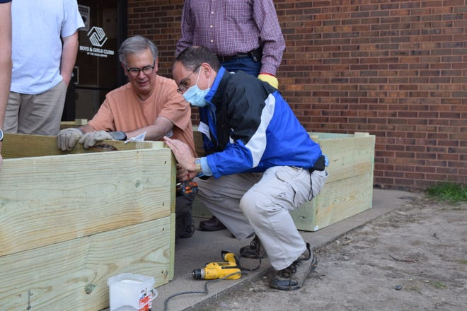 Two volunteers use a a screwdriver to build a teaching garden for the Boys and Girls Club on May 12, 2021.