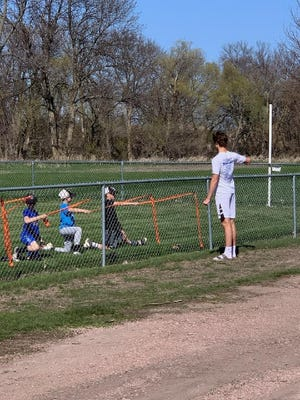 Jack Henry teaches kids arm band stretches at a pitching clinic in Dell Rapids on April 29, 2021.