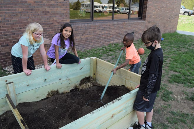 Members of the Boys and Girls Club fill a teaching garden with soil. As the summer goes on, they'll use the garden to learn about plant lifecycles, where their food comes from and more.