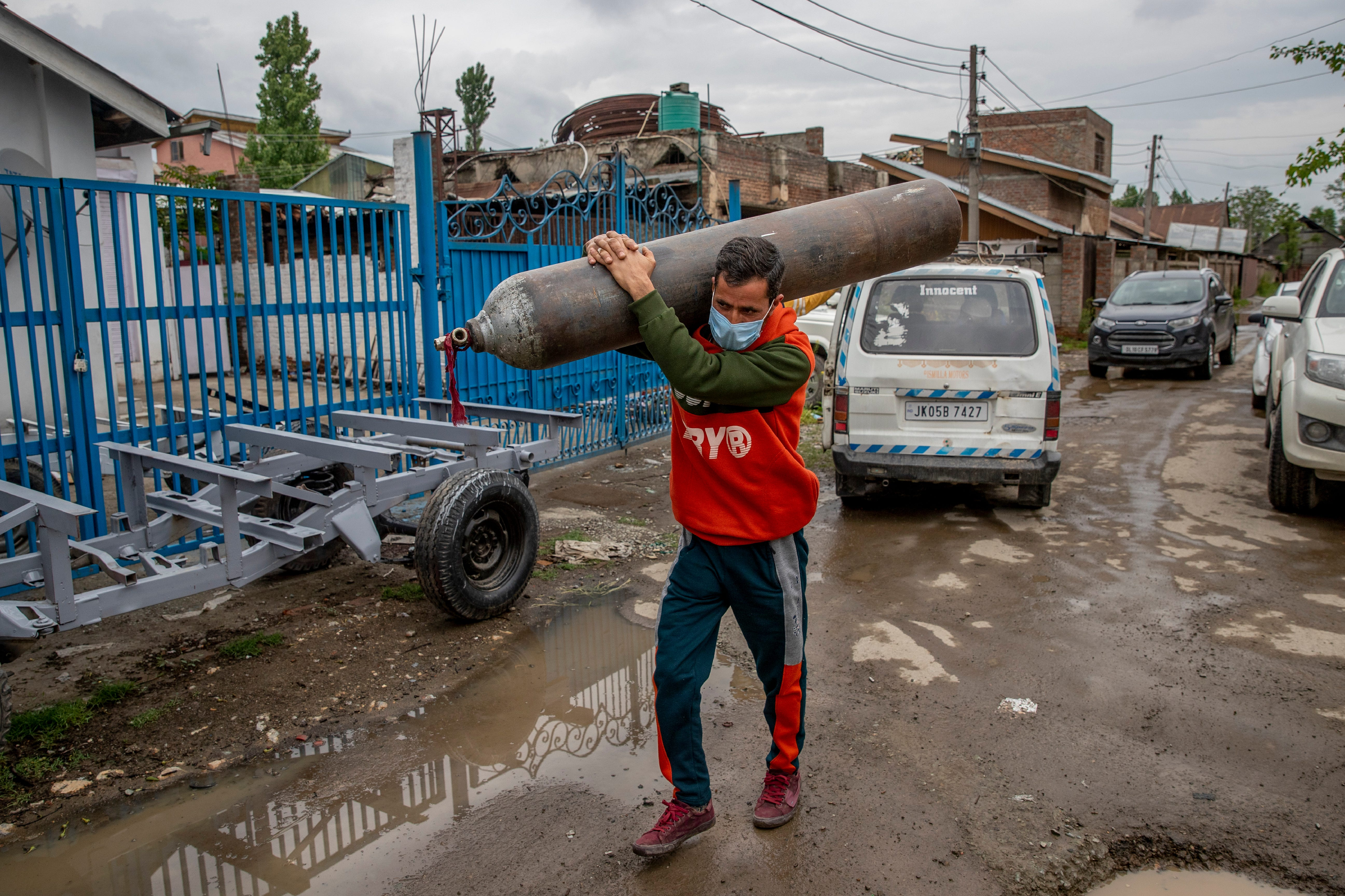 Showkat Ahmed War carries an empty oxygen cylinder to get it refilled at a gas supplier facility in Srinagar, Kashmir, which is controlled by India, on May 11, 2021. War traveled about 40 miles to refill the cylinder needed for his ailing father due to the huge demand for oxygen after the surge in COVID-19 cases.