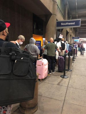 Southwest Airlines passengers in line for curbside check-in at Phoenix Sky Harbor International Airport in May.
