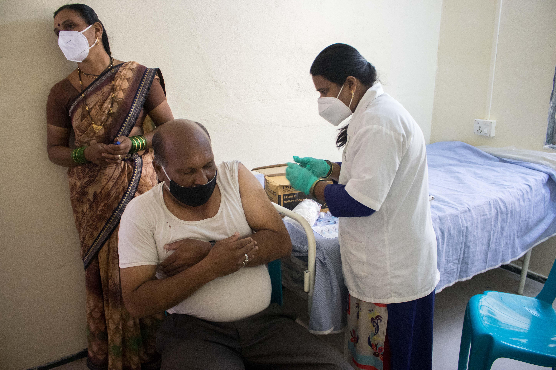 Jaidee Meshram, an auxiliary nurse midwife, vaccinates a man against COVID-19 in Tardal village in Maharashtra, India.