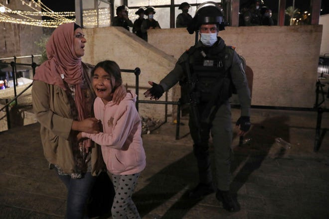 An Israeli police officer gestures to a Palestinian woman and her daughter, frightened by clashes outside of the Damascus Gate to the Old City of Jerusalem Tuesday, May 11, 2021.