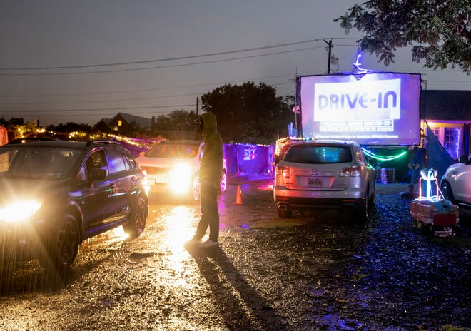"""John Brown ushers cars to their screening at the Blue Starlite Mini Urban Drive-In on April 30. Three screenings were scheduled that night at the East Austin location: """"Back to the Future,"""" """"Sixteen Candles"""" and """"Indiana Jones and the Last Crusade."""""""