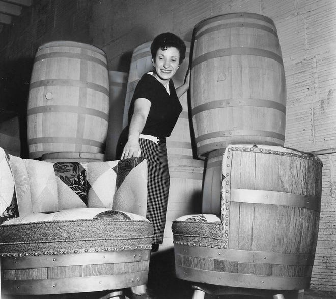 San Hygene office worker Mary Lou Bolas admires a selection of bourbon barrel chairs ready for shipment May 22, 1959, at the Akron factory.