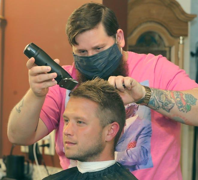LaBelle's Barber Parlor owner Charles LaBelle II cuts Derek McDaniel's hair on Thursday in Akron.