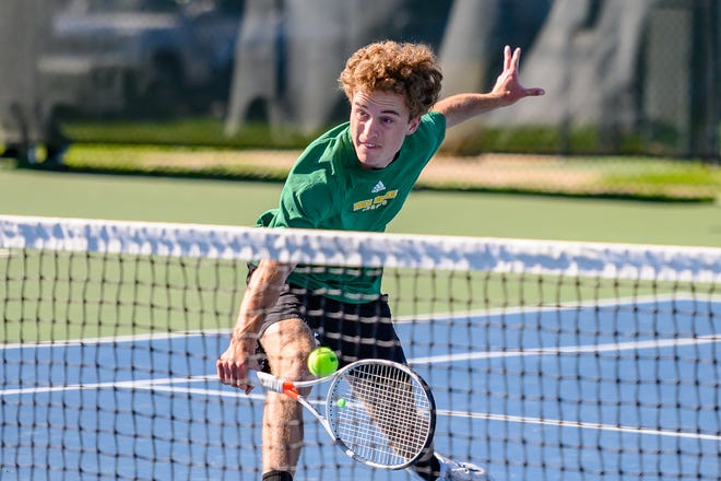 Rock Bridge's Will McAllister reaches for a front-court volley during doubles play against Hickman in the Class 3 District 4 championship Wednesday at Cosmo-Bethel Park.