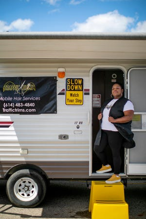 Bry Sims cuts hair out of her mobile barber shop on South High Street on May 11. With one chair, running water and a shampoo sink, it's all she needs to be independent.