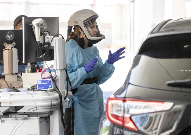 Physician assistant Jennifer Krzmarzick talks to a patient in a car after performing a swab test for COVID-19 during a trial run for an outdoor emergency triage at Mt. Carmel East hospital in April 2020.
