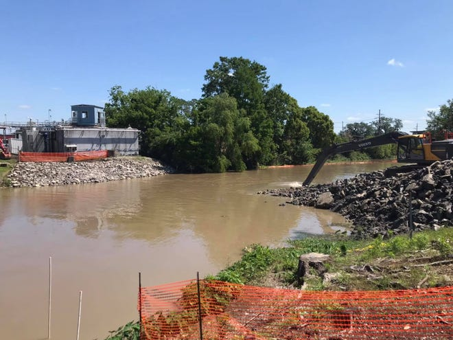 Workers remove a weir in Bayou Lafourche in Thibodaux earlier this year. The project was completed in May.