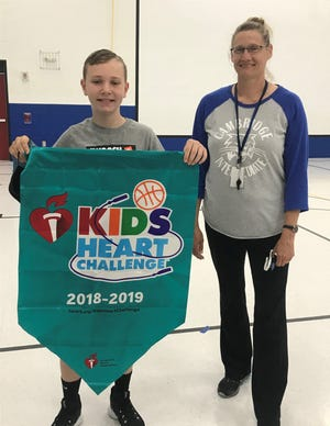 A.J. Lawrence, a fifth grader at Cambridge Intermediate School, poses with physical education teacher Sheryl Taylor and a banner from a previous year. Lawrence raised approximately $5,000 for the American Heart Association in honor of his late grandfather.