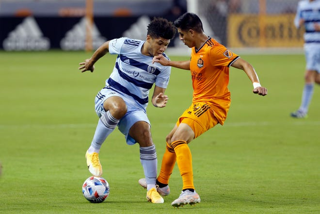 Sporting Kansas City defender Jaylin Lindsey, left, tries to work the ball around Houston Dynamo midfielder Joe Corona (14) during the first half of an MLS soccer match Wednesday in Houston. Houston blanked Sporting KC 1-0.