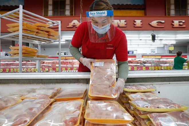 In this April 29, 2020 file photo, a worker restocks chicken in the meat product section at a grocery store in Dallas. Rising prices for a variety of commodities are contributing to a jump in prices at the consumer level in 2021, with Americans paying more for meat, gasoline, items they keep in their homes and even the homes themselves.