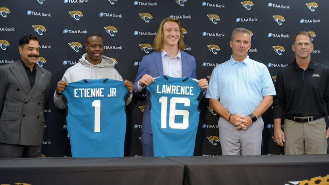 After his arrival in Jacksonville, Florida Friday morning, April 30, 2021, Jacksonville Jaguars first-round draft pick Trevor Lawrence along with team owner Shad Khan, head coach Urban Meyer and the Jaguars general manager Trent Baalke held a press conference in the afternoon inside TIAA Bank Field. They were also joined by the Jaguars 25th pick in the first round of the draft and former Clemson teammate of Lawrence, running back Travis Etienne. [Bob Self/Florida Times-Union]