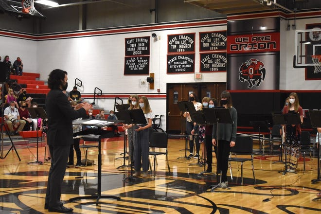 """Directed by Parker Haley, left, the combined choir sings """"Carriers of Light"""" during Orion Middle School's Fine Arts Festival on Wednesday, May 5, at Orion High School. Because of COVID-19 restrictions, it was the first concert for a live audience in 2020-21."""