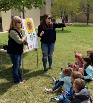 Stephanie Eckroat and Sathena Scarborough teach students about sunflowers at Holy Family Elementary School in Hays.