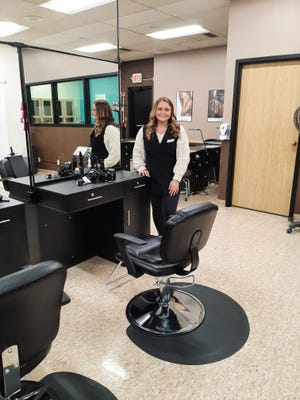 Maggie Sosnowski poses by her work and school home for almost two years as she participated in the CareerTec program offered at Highland Community College's Cosmetology Department.