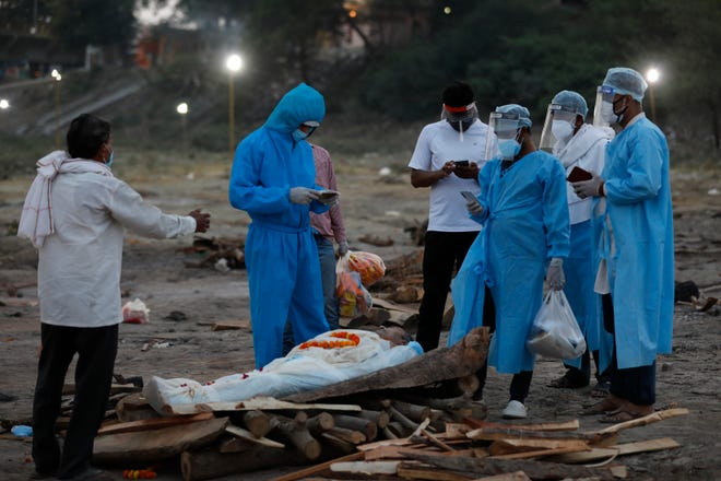 Family members pay last respects to their relative Rajendra Prasad Mishra, a 62-year-old man who has lost his life from coronavirus infection before cremation at River Ganges at Phaphamau in Prayagraj, India. (AP Photo/Rajesh Kumar Singh)