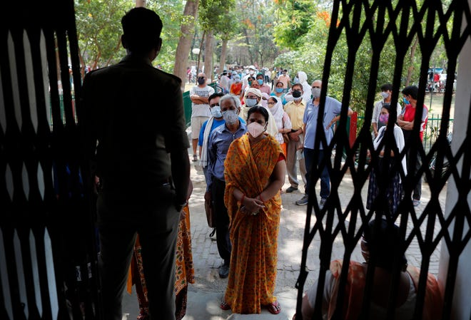 Indians line up to receive the vaccine for COVID-19 at a medical college in Prayagraj, India. Two southern states in India became the latest to declare lockdowns, as coronavirus cases surge at breakneck speed across the country and pressure mounts on Prime Minister Narendra Modi's government to implement a nationwide shutdown.  (AP Photo/Rajesh Kumar Singh)