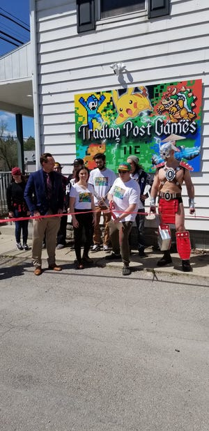 Jericho England (center) cuts the ribbon to mark the grand opening of his new game store, Trading Post Games, located in downtown Temperance. England is surrounded by friends and employees, along with his wife, Sarah (left) and Bedford Township Supervisor Paul Pirrone.