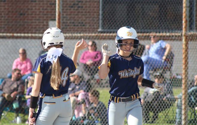 Aly VanBrandt (right) gets a high five from Whiteford teammate Berlynn Keller after scoring a run. Both have been named to the All-Tri-County Conference softball team.