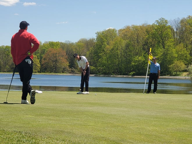 Hackettstown junior Derek Weaver, center, putts on the final green of the Clubview course during the Hunterdon/Warren/Sussex Tournament on May 13, 2021, in Andover. Weaver shot a 1-under 71 to win the tri-county title.