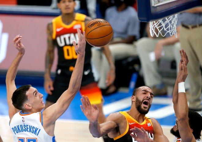 Oklahoma City's Aleksej Pokusevski (17) fights Utah's Rudy Gobert (27) for a rebound on Dec. 28 at Chesapeake Energy Arena.